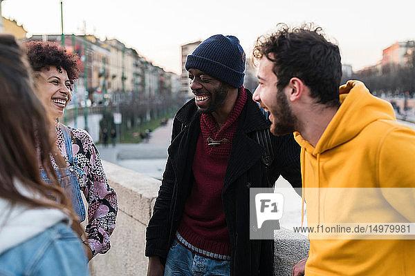 Vier erwachsene Freundinnen und Freunde unterhalten sich und lachen am Ufer des Stadtkanals