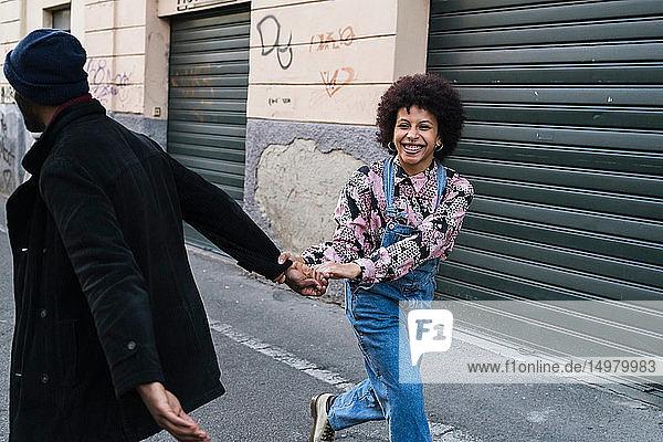 Junges Paar albert in einer Stadtgasse Händchen haltend herum