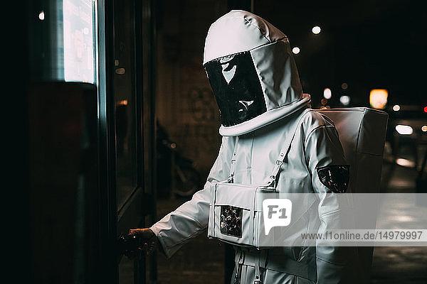 Astronaut öffnet nachts die Tür zum Einkaufen