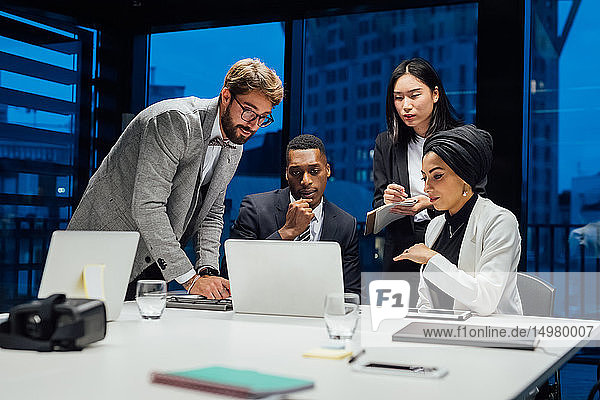 Businesswomen and men looking at laptop during conference table meeting