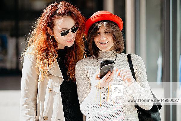 Weibliche Käuferinnen mit Smartphone vor dem Geschäft