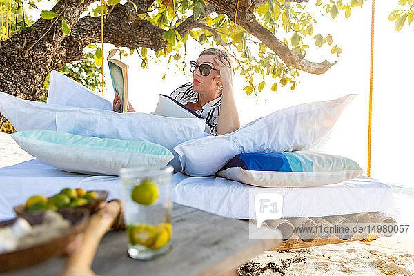 Frau liest Buch auf Schaukelbett am Strand  Insel Ginto  Linapacan  Philippinen