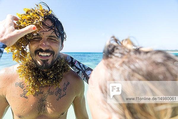 Frau wickelt im Meer Seetang um den Hals des Mannes  Pagudpud  Ilocos Norte  Philippinen