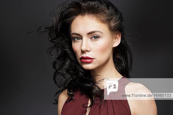 Schöne junge Frau mit langen schwarzen Haaren  Studioporträt