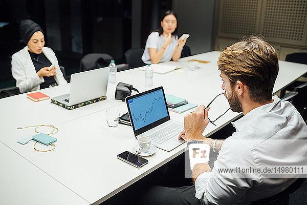 Geschäftsfrau betrachtet Laptop und Smartphones am Konferenztisch
