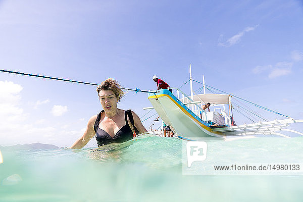 Frau verlässt das im Meer vertäute Boot  Insel Ginto  Linapacan  Philippinen