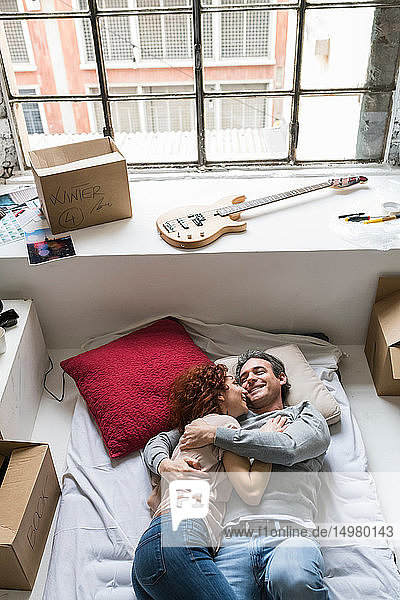 Couple moving into industrial style apartment  lying on mattress hugging