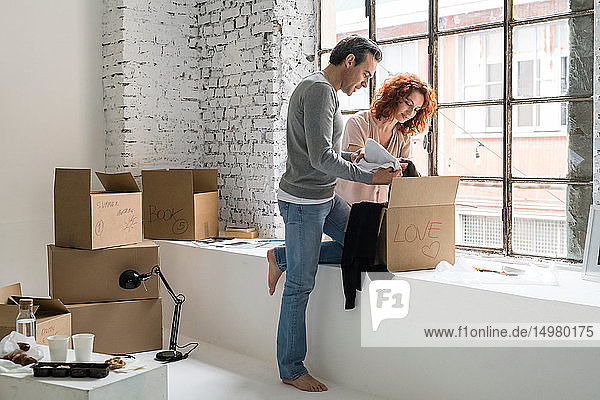 Romantic couple moving into industrial style apartment  unpacking cardboard box with loveheart