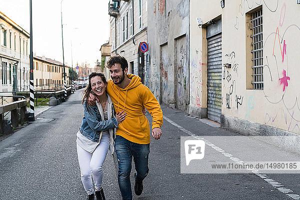 Glückliches junges Paar geht mit umarmten Armen durch die Gasse