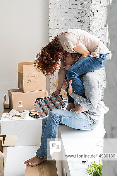 Romantic couple moving into industrial style apartment  woman sitting on boyfriend's shoulders holding photographs