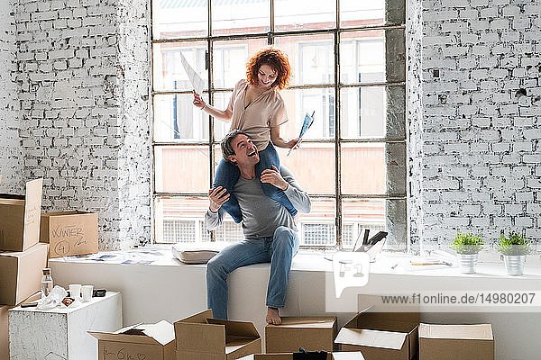 Couple moving into industrial style apartment  woman sitting on boyfriend's shoulders holding paperwork