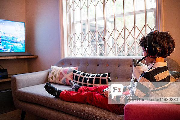 Junge sitzt auf dem Sofa und spielt Videospiel mit dem Game-Controller