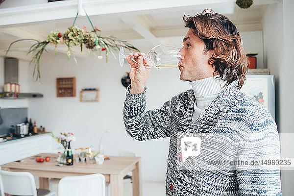 Man drinking white wine in loft office