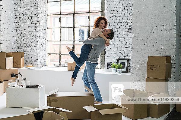Ehepaar zieht in eine Wohnung im Industriestil  Mann hebt Freundin hoch