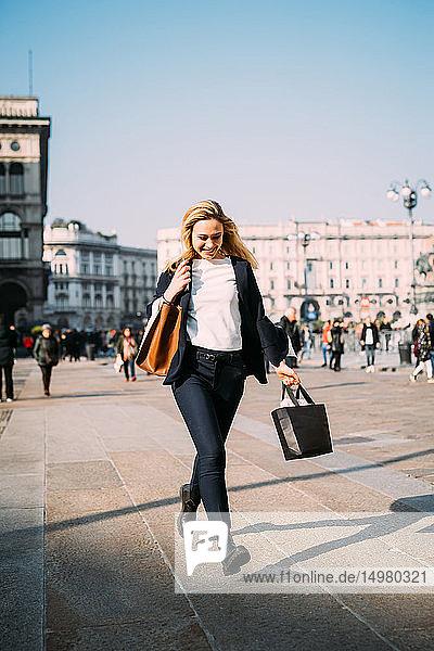 Junge Touristin mit Einkaufstaschen spaziert auf dem Stadtplatz  Mailand  Italien