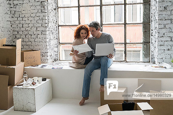 Couple moving into industrial style apartment  sitting on window ledge looking at photograph