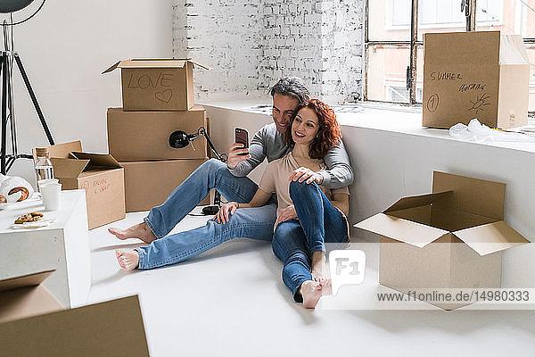 Ehepaar zieht in eine Wohnung im Industriestil  sitzt auf dem Boden und schaut auf ein Smartphone