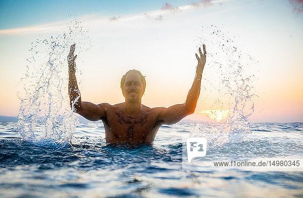 Mann plätschert bei Sonnenuntergang im Meer  Pagudpud  Ilocos Norte  Philippinen