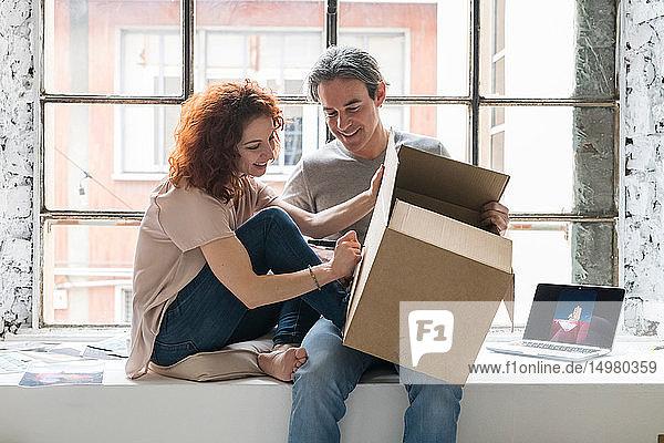 Ehepaar zieht in eine Wohnung im Industriestil  sitzt auf Fensterbrettern und schreibt auf Pappkarton