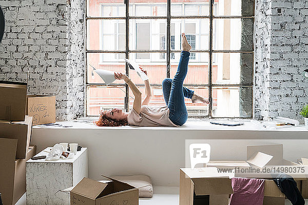 Mid adult woman moving into industrial style apartment  lying on window ledge looking at photographs