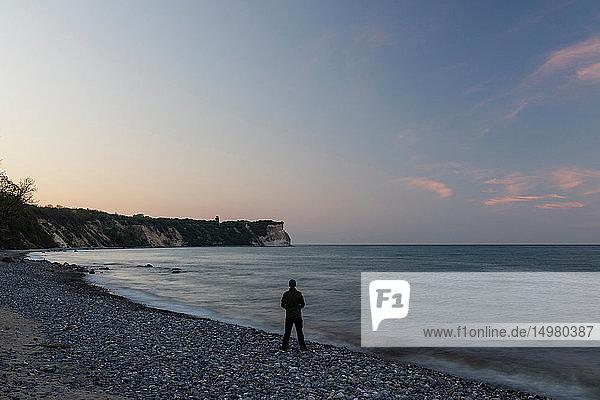 Mann schaut bei Sonnenuntergang vom Strand hinaus  Putgarten  Rugen  Mecklenburg-Vorpommern  Deutschland