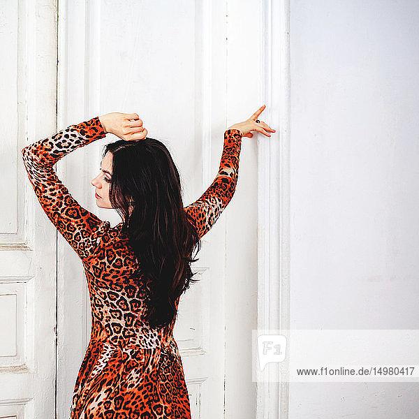 Woman posing in front of white door