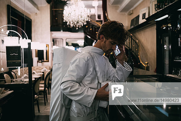 Astronaut mit Smartphone im Restaurant