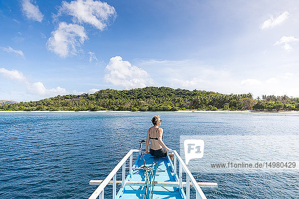 Woman sitting on bow of boat heading to island  Ginto island  Linapacan  Philippines