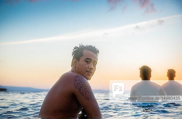 Mann und Freunde genießen das Meer bei Sonnenuntergang  Pagudpud  Ilocos Norte  Philippinen