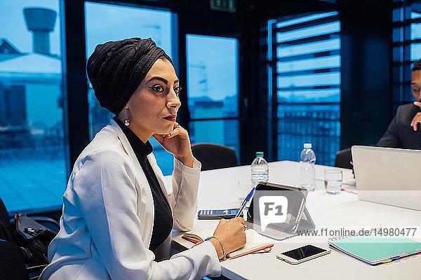 Geschäftsfrau hört bei Konferenztisch-Sitzung zu