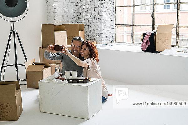Ehepaar zieht in eine Wohnung im Industriestil  sitzt auf dem Boden und nimmt sich selbst