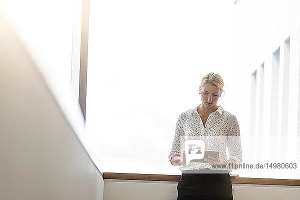 Geschäftsfrau benutzt digitales Tablett im Korridor