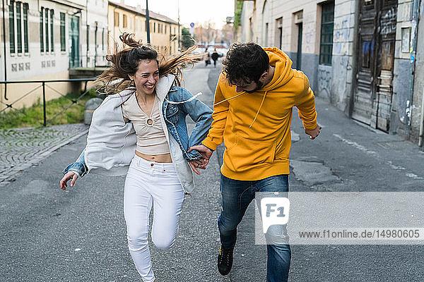 Junges Paar hält sich an der Hand und läuft durch die Gasse der Stadt