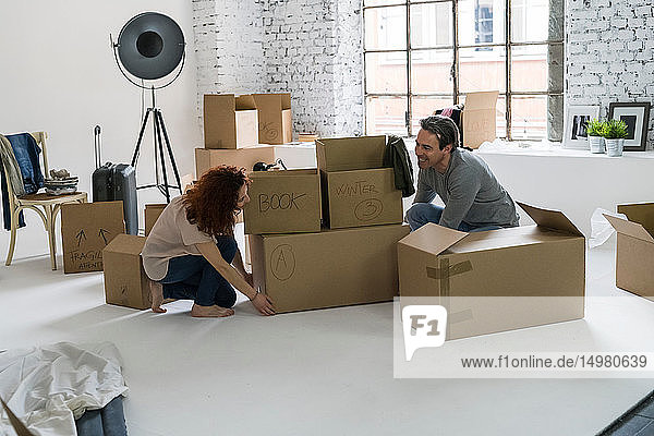 Couple moving into industrial style apartment  stacking cardboard boxes