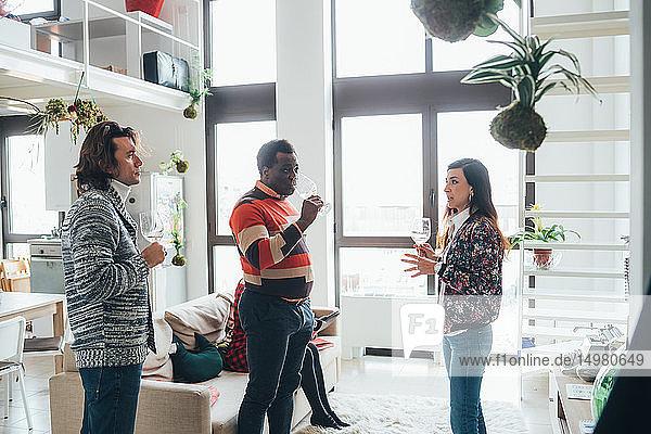 Friends talking at party in loft office