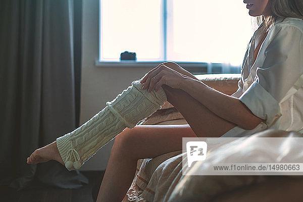 Frau in Dessous zieht Beinwärmer auf dem Bett an