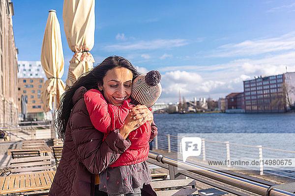 Mutter umarmt Tochter am Fluss  Berlin  Deutschland