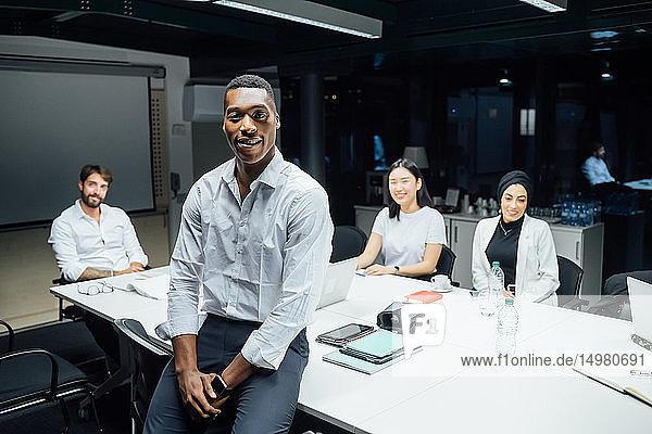 Junger Geschäftsmann vor dem Team bei Konferenztisch-Sitzung  Porträt
