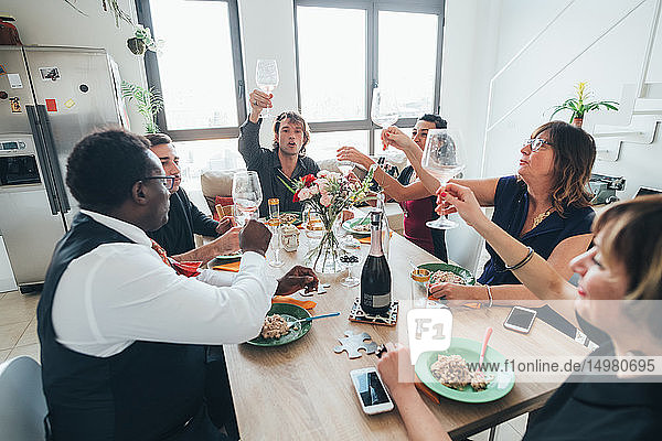 Businessmen and businesswomen celebrating at lunch party in loft office