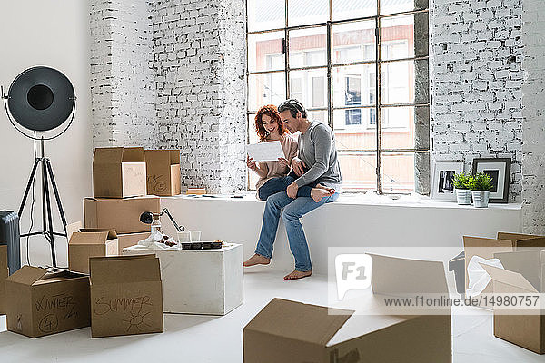 Couple moving into industrial style apartment  sitting on window ledge looking at photo