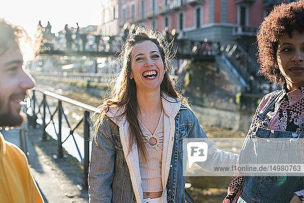 Drei weibliche und männliche junge erwachsene Freunde unterhalten sich am Ufer des Stadtkanals