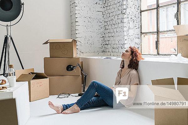 Mittlere erwachsene Frau sitzt entspannt auf dem Boden und zieht in eine Wohnung im Industriestil