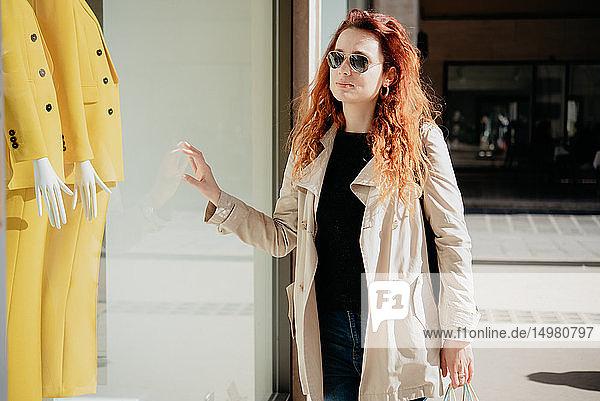 Frau schaut in Schaufenster einer Modeboutique