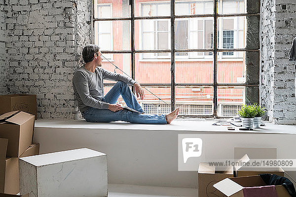 Man moving into industrial style apartment  sitting on window ledge looking through window