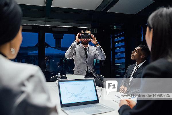 Geschäftsmann blickt während eines Konferenztischgesprächs durch ein Virtual-Reality-Headset