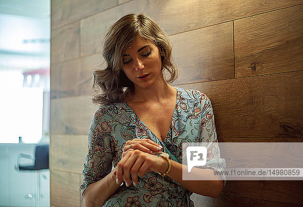 Frau kontrolliert die Zeit  lehnt an Holzwand