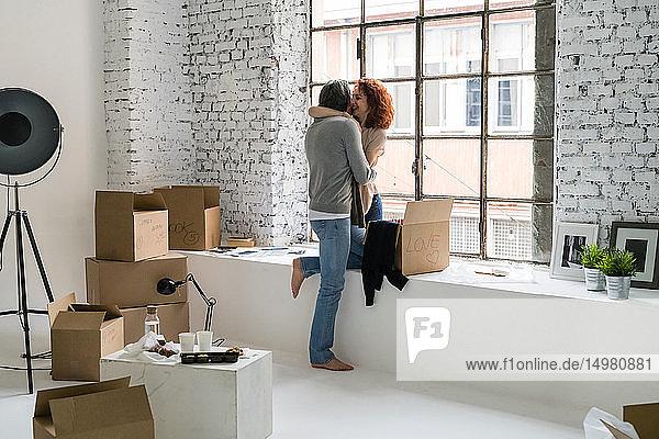 Romantisches Paar zieht in eine Wohnung im Industriestil und umarmt sich
