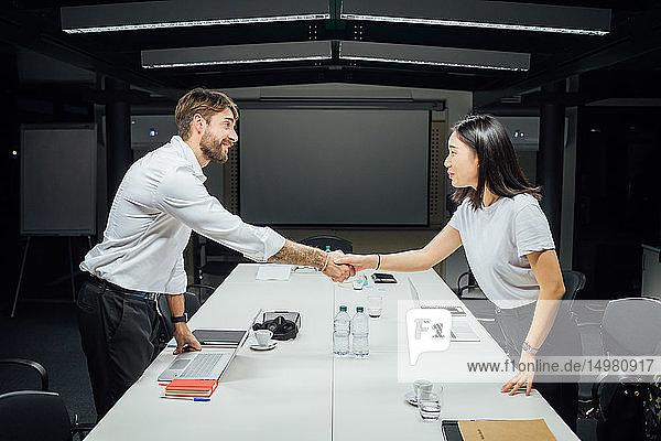 Geschäftsfrau und Mann schütteln sich die Hand am Konferenztisch