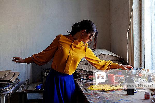 Woman creating art with scraper