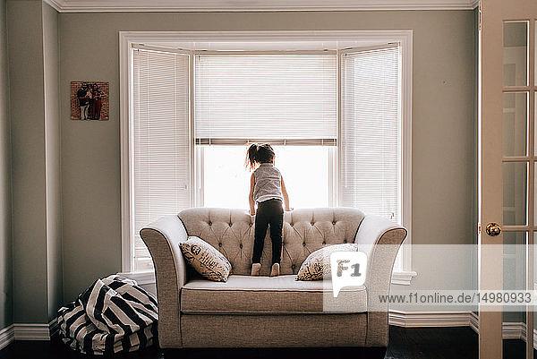 Auf Sofa stehendes Mädchen schaut durch Wohnzimmerfenster  Rückansicht